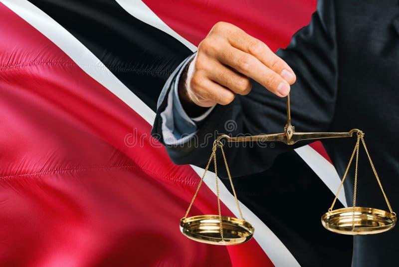 Ο δικαστής κρατά τις χρυσές κλίμακες της δικαιοσύνης με το κυματίζοντας υπόβαθρο σημαιών του Τρινιδάδ και Τομπάγκο Θέμα ισότητας  στοκ εικόνα