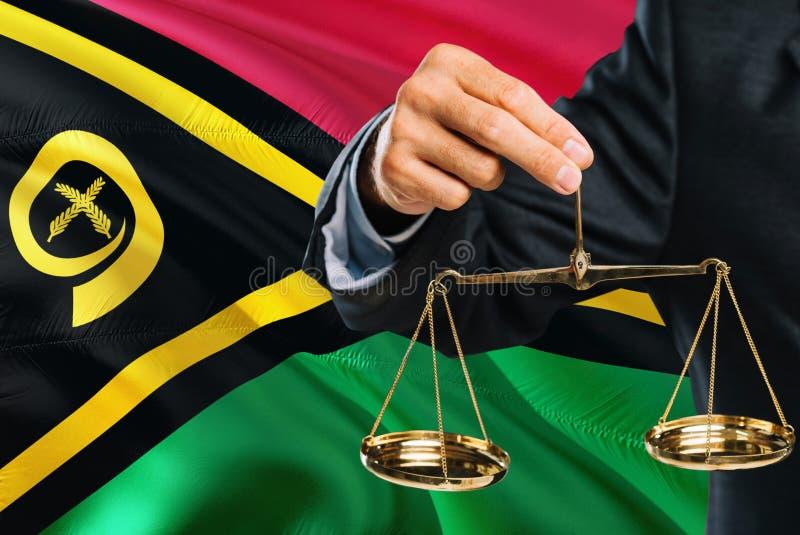 Ο δικαστής κρατά τις χρυσές κλίμακες της δικαιοσύνης με το κυματίζοντας υπόβαθρο σημαιών του Βανουάτου Θέμα ισότητας και νομική έ στοκ εικόνα