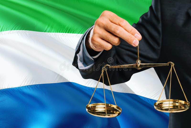 Ο δικαστής κρατά τις χρυσές κλίμακες της δικαιοσύνης με το Sierra Leone που κυματίζει το υπόβαθρο σημαιών Θέμα ισότητας και νομικ στοκ φωτογραφία με δικαίωμα ελεύθερης χρήσης