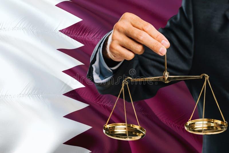 Ο δικαστής Qatari κρατά τις χρυσές κλίμακες της δικαιοσύνης με το κυματίζοντας υπόβαθρο σημαιών του Κατάρ Θέμα ισότητας και νομικ στοκ εικόνες