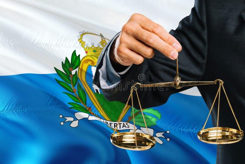 Ο δικαστής Sammarinese κρατά τις χρυσές κλίμακες της δικαιοσύνης με το κυματίζοντας υπόβαθρο σημαιών του Άγιου Μαρίνου Θέμα ισότη στοκ φωτογραφία με δικαίωμα ελεύθερης χρήσης
