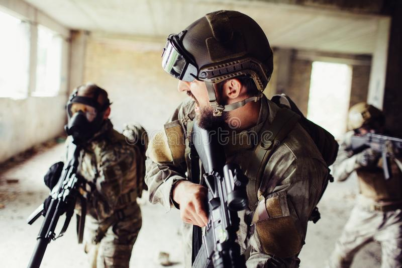 Ο διοικητής στέκεται σε ένα μέτωπο και κοιτάζει στους στρατιώτες του Όλοι κρατούν τα τουφέκια Τα άτομα στην πλάτη φορούν ομοιόμορ στοκ εικόνες