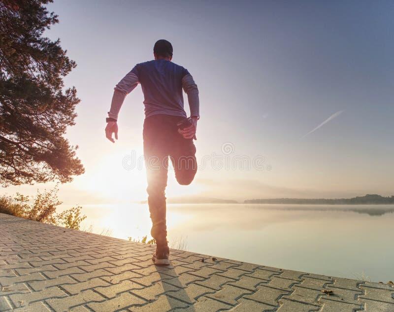 Ο δρομέας ατόμων που κάνει την τεντώνοντας άσκηση, προετοιμάζει το σώμα για το workout στοκ φωτογραφίες