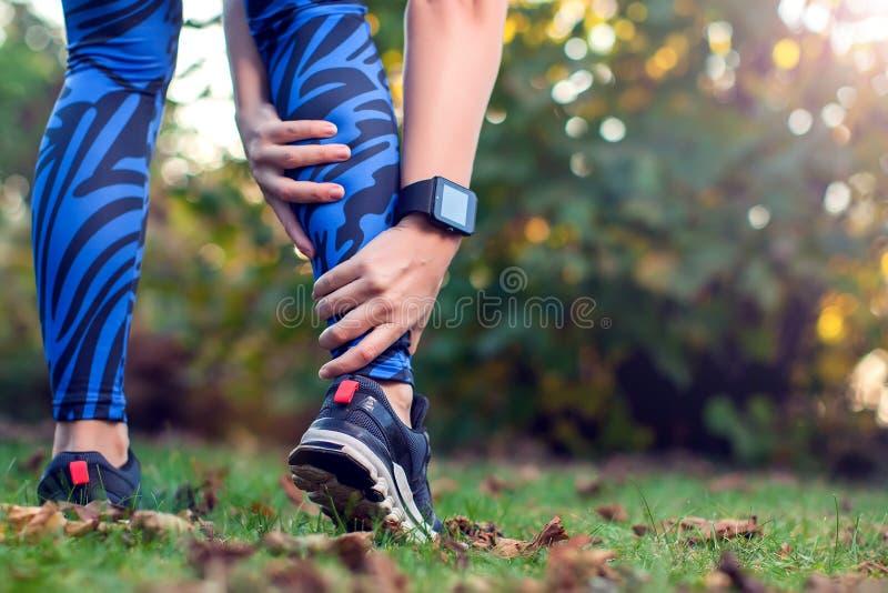 Ο δρομέας γυναικών κρατά τραυματισμένο το αθλητισμός πόδι της Αθλητισμός, ιατρική και pe στοκ εικόνες