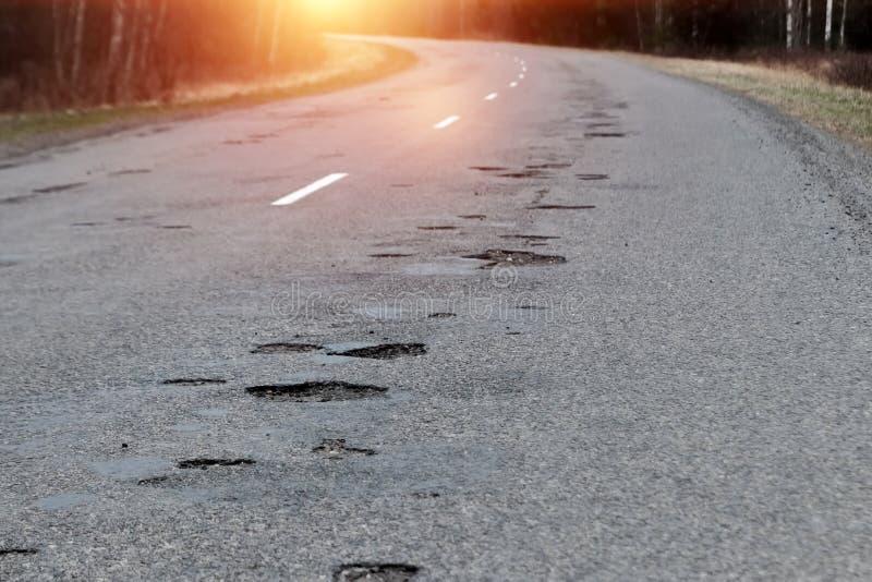Ο δρόμος στην ερείπωση με πολλές λακκούβες Τα αυτοκίνητα πηγαίνουν με τον κίνδυνο διακοπών στοκ φωτογραφία με δικαίωμα ελεύθερης χρήσης