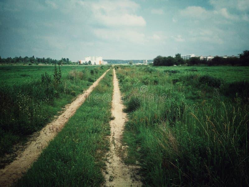 Ο δρόμος στον τομέα που οδηγείται με τα αυτοκίνητα Δύο πάροδοι από τις ρόδες που φεύγουν στην απόσταση Πράσινη χλόη στοκ φωτογραφίες με δικαίωμα ελεύθερης χρήσης