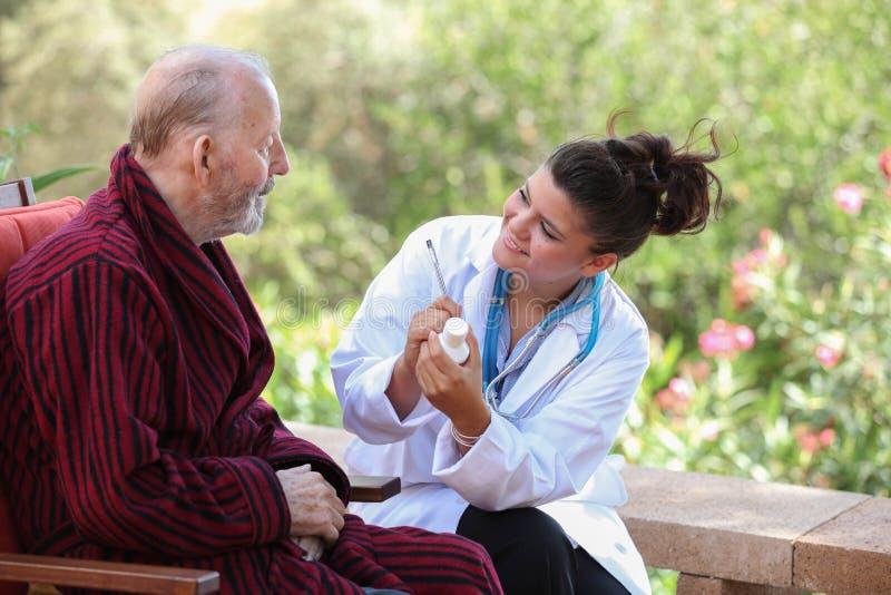 Ο Δρ ή νοσοκόμα που δίνει το φάρμακο στον ανώτερο ασθενή στοκ φωτογραφία με δικαίωμα ελεύθερης χρήσης