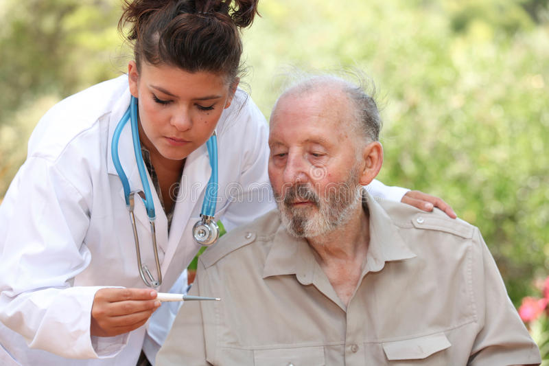 Ο Δρ θερμόμετρο ανάγνωσης του ανώτερου ατόμου στοκ εικόνες με δικαίωμα ελεύθερης χρήσης