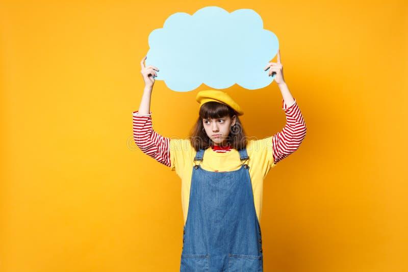 Ο δυσαρεστημένος έφηβος κοριτσιών γαλλικό beret, μπλε κενό κενό λαβής τζιν sundress λέει το σύννεφο, λεκτική φυσαλίδα που απομονώ στοκ φωτογραφία