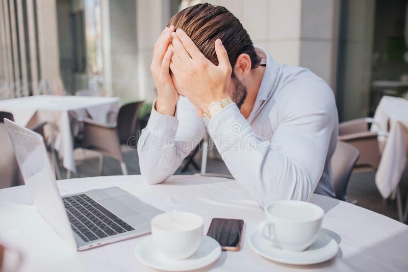Ο δυστυχισμένος και λυπημένος νεαρός άνδρας κάθεται στον πίνακα στο εστιατόριο Έκλεισε το πρόσωπό του με τα χέρια Ο τύπος είναι σ στοκ εικόνα