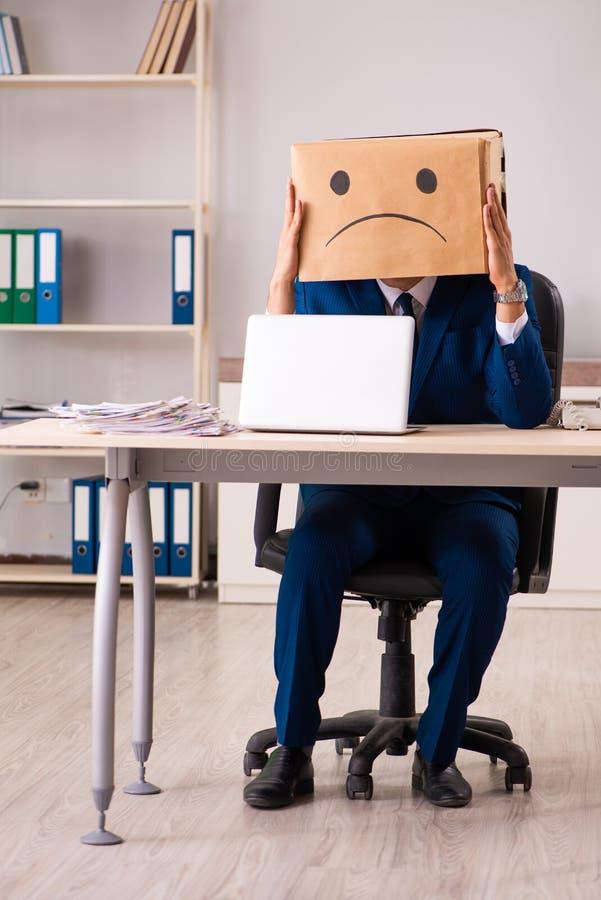 Ο δυστυχισμένος υπάλληλος ατόμων με το κιβώτιο αντί του κεφαλιού του στοκ εικόνα με δικαίωμα ελεύθερης χρήσης
