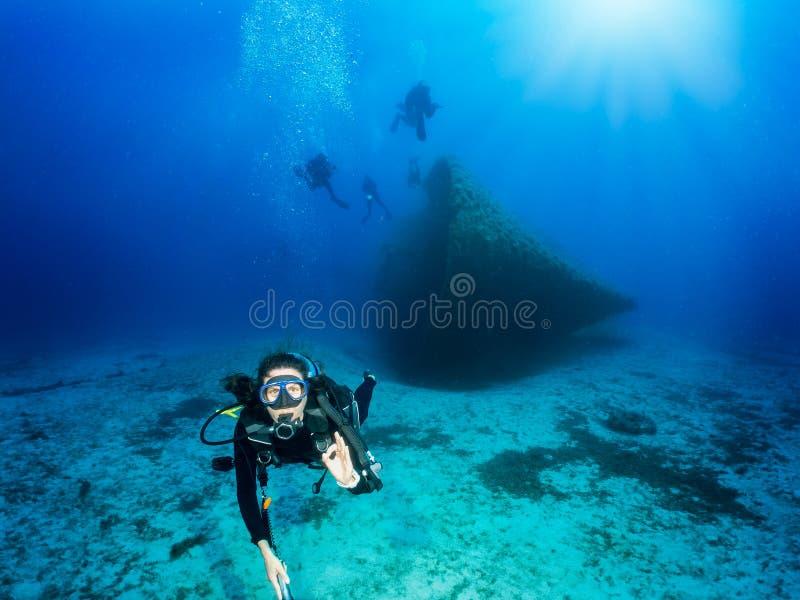 Ο δύτης σκαφάνδρων παρουσιάζει ΕΝΤΑΞΕΙ σημάδι στο μπλε, Αιγαίο πέλαγος στην Ελλάδα στοκ εικόνα