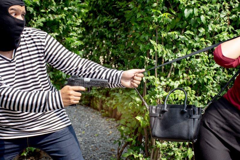 Ο εγκληματίας κλεφτών ληστών με το πυροβόλο όπλο που στέκεται πίσω από τις ασιατικές γυναίκες και για να έρθει ο πλησιέστερα για  στοκ εικόνα με δικαίωμα ελεύθερης χρήσης