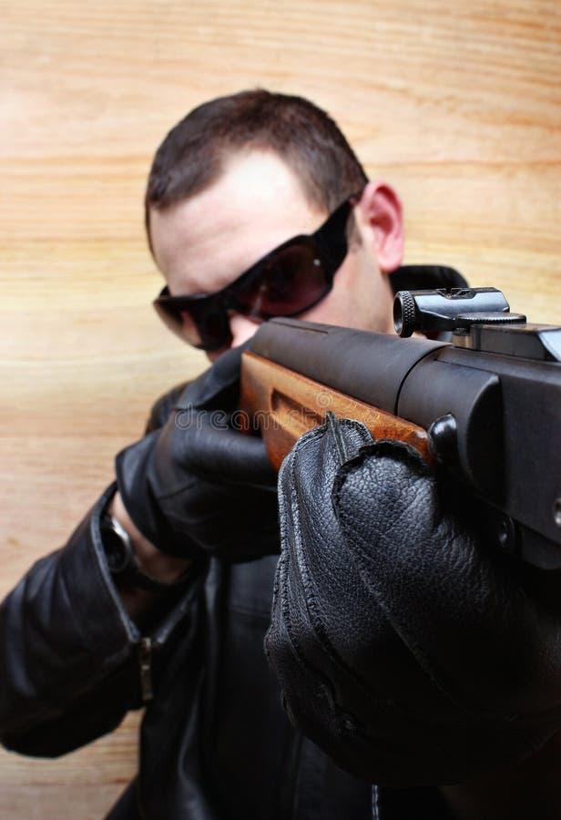 Ο εγκληματίας μαφιών γκάγκστερ πυροβολεί ένα πυροβόλο όπλο στοκ εικόνες