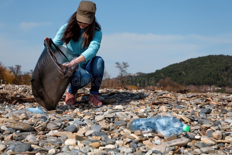 Ο εθελοντής γυναικών βοηθά να καθαρίσει την παραλία των πλαστικών απο στοκ εικόνες
