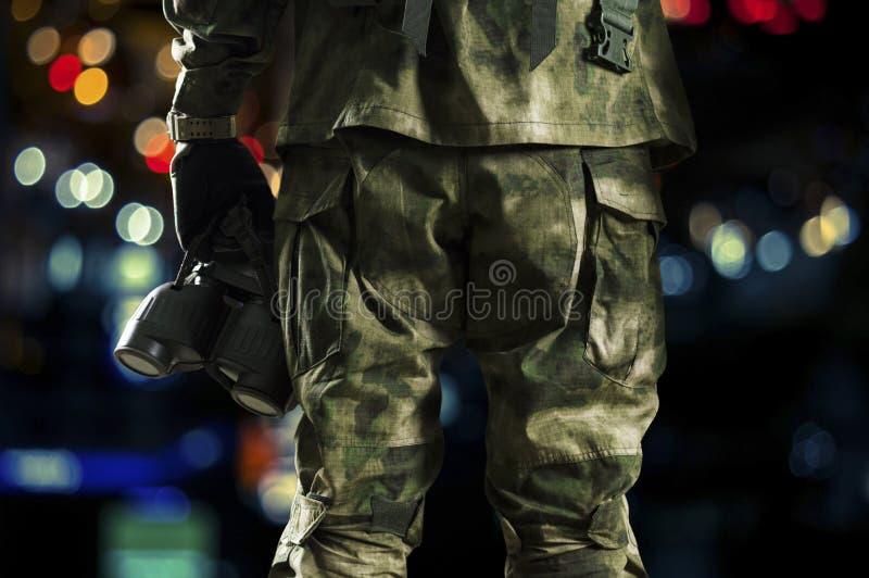 Ο ειδικός στρατιώτης μονάδων κρατά μια συσκευή νυχτερινής όρασης στο χέρι του στοκ εικόνες