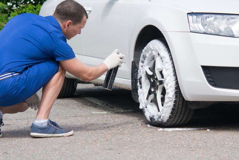 Ο ειδικός συντήρησης αυτοκινήτων, προστατεύει και καθαρίζει τις ρόδες, από το ρύπο και τη γήρανση στοκ εικόνες
