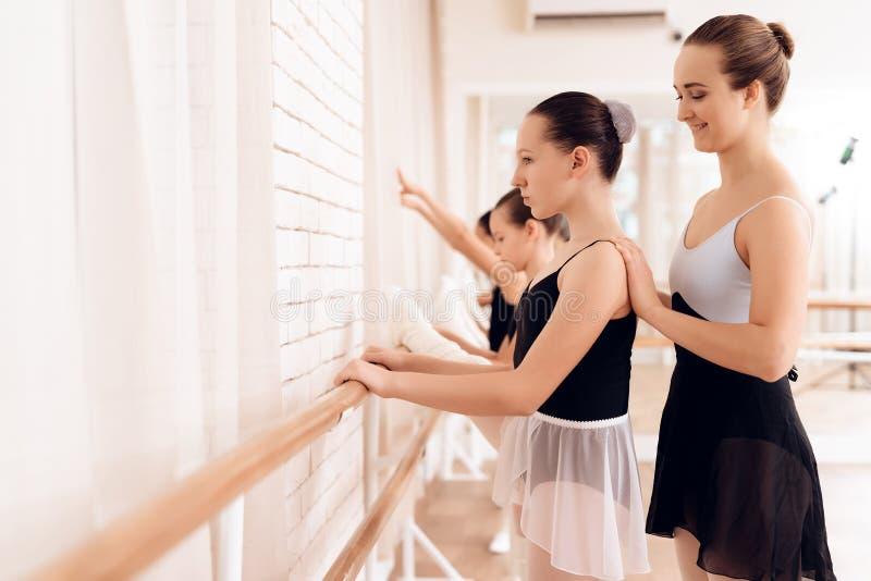 Ο εκπαιδευτής του σχολείου μπαλέτου βοηθά τα νέα ballerinas να εκτελέσουν τις διαφορετικές χορογραφικές ασκήσεις στοκ φωτογραφίες