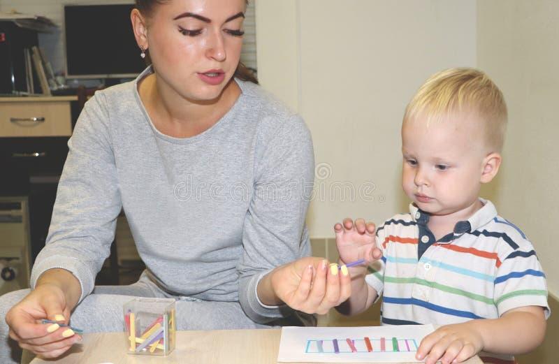 Ο εκπαιδευτικός εξετάζει το παιδί στον παιδικό σταθμό Δημιουργικότητα και ανάπτυξη του παιδιού στοκ φωτογραφία