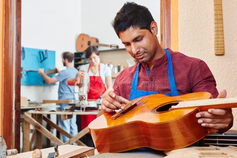 Ο εκπαιδευόμενος του κατασκευαστή κιθάρων επισκευάζει την κιθάρα στοκ εικόνες