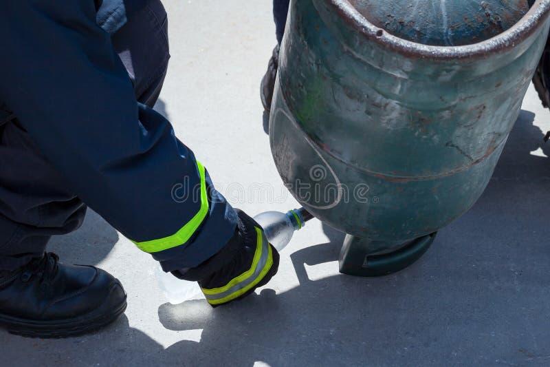 Ο εκπαιδευτής πυρκαγιάς, χύνοντας υγρά LPG δηλητηριάζει με αέρια στο μπουκάλι από την άνω πλευρά - κάτω στοκ φωτογραφία με δικαίωμα ελεύθερης χρήσης