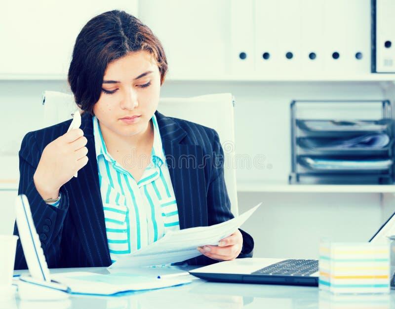 Ο εκπαιδευόμενος διαβάζει τα έγγραφα για τη συναλλαγή στοκ εικόνα