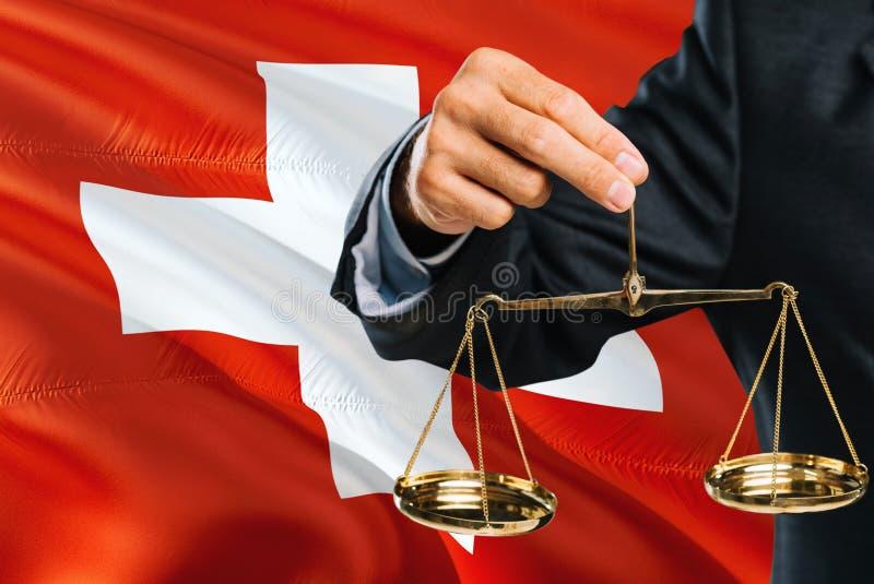 Ο ελβετικός δικαστής κρατά τις χρυσές κλίμακες της δικαιοσύνης με το κυματίζοντας υπόβαθρο σημαιών της Ελβετίας Θέμα ισότητας και στοκ εικόνα με δικαίωμα ελεύθερης χρήσης