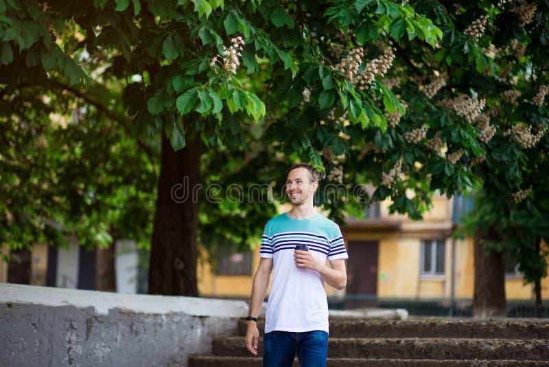 Ο ελκυστικός νεαρός άνδρας με τη σκοτεινή τρίχα περπατά την οδό με ένα φλιτζάνι του καφέ μια ηλιόλουστη ημέρα στοκ εικόνες με δικαίωμα ελεύθερης χρήσης