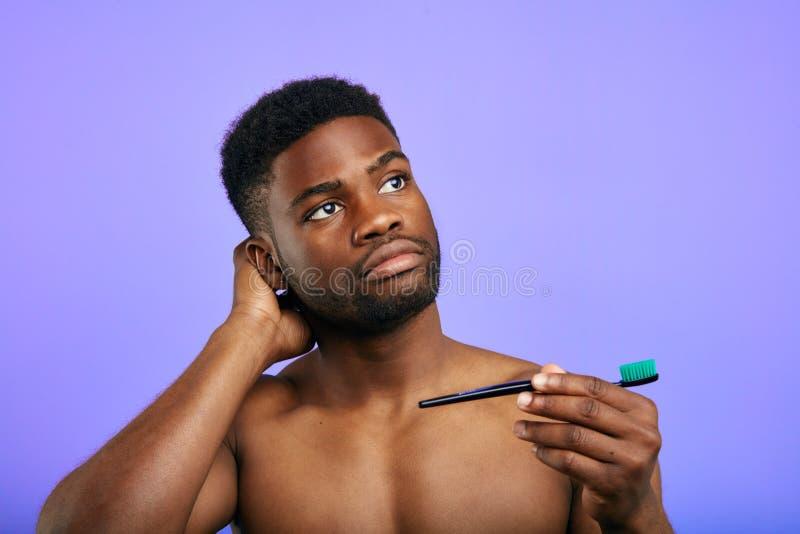 Ο ελκυστικός στοχαστικός τύπος στέκεται με τη βούρτσα για τα δόντια στοκ εικόνα με δικαίωμα ελεύθερης χρήσης
