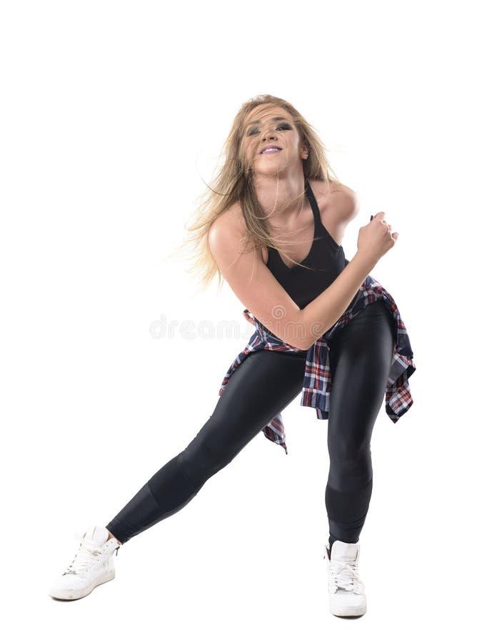 Ο εμπαθής ενεργητικός ενεργός εκπαιδευτικός αερόμπικ χορού γυναικών που κάμφθηκε προς τα εμπρός με η τρίχα πέρα από το πρόσωπο στοκ εικόνες