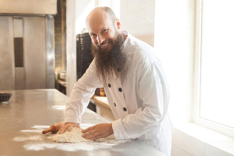 Ο ενήλικος αρτοποιός με τη μακριά γενειάδα στην άσπρη ομοιόμορφη στάση στον εργασιακό χώρο και προετοιμάζει τη ζύμη ψωμιού με τα  στοκ εικόνα