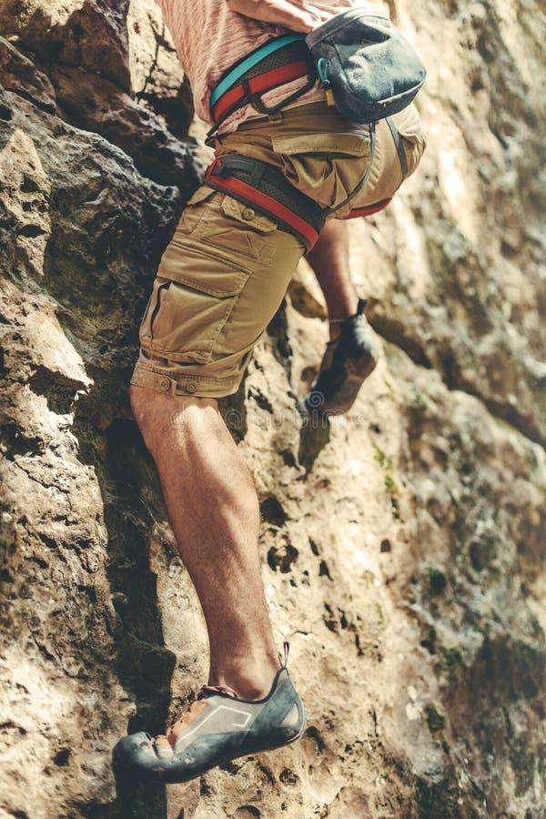 Ο ενήλικος αρσενικός ορεσίβιος στο λουρί ασφάλειας αναρριχείται σε έναν τοίχο βράχου Ακραία έννοια δραστηριότητας χόμπι υπαίθρια στοκ φωτογραφία με δικαίωμα ελεύθερης χρήσης