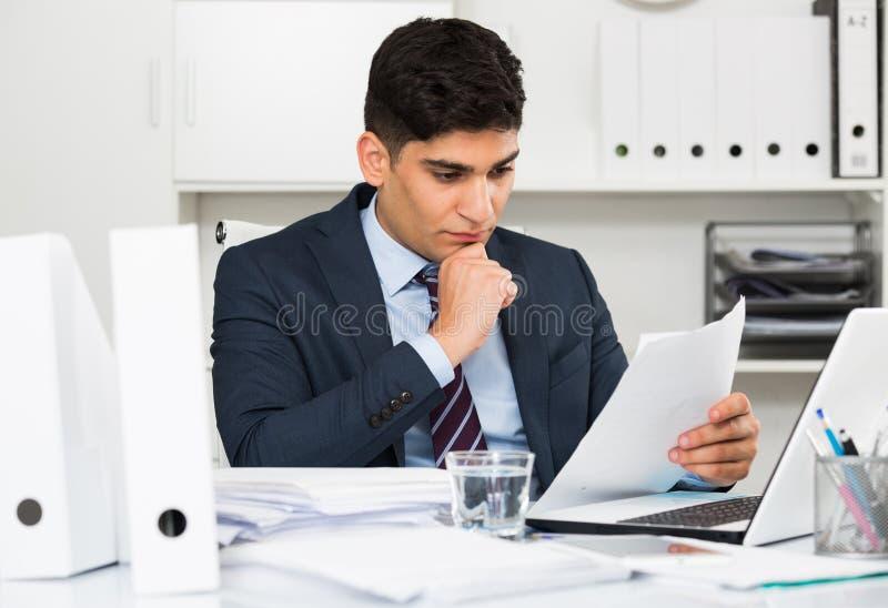 Ο ενήλικος εργαζόμενος γραφείων διαβάζει τα έγγραφα για τη συναλλαγή στοκ φωτογραφία