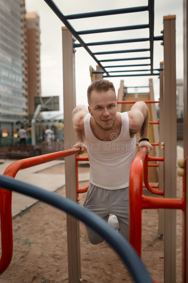Ο ενεργητικός νεαρός άνδρας κάνει τις ασκήσεις υπαίθρια στο αθλητικό τετράγωνο στο kee στοκ φωτογραφία με δικαίωμα ελεύθερης χρήσης