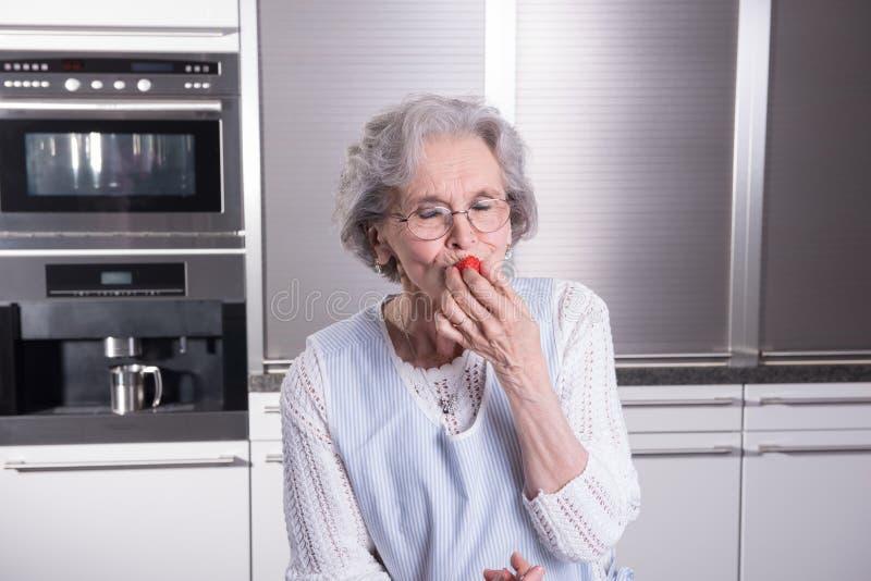 Ο ενεργός θηλυκός συνταξιούχος δοκιμάζει τις φράουλες στην κουζίνα στοκ φωτογραφίες με δικαίωμα ελεύθερης χρήσης