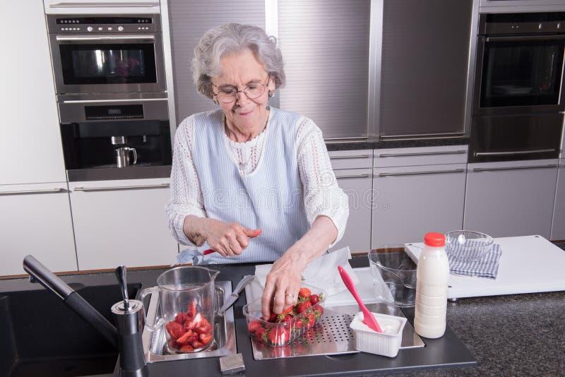 Ο ενεργός θηλυκός συνταξιούχος προετοιμάζει και τρώει τις φράουλες μέσα στοκ φωτογραφία