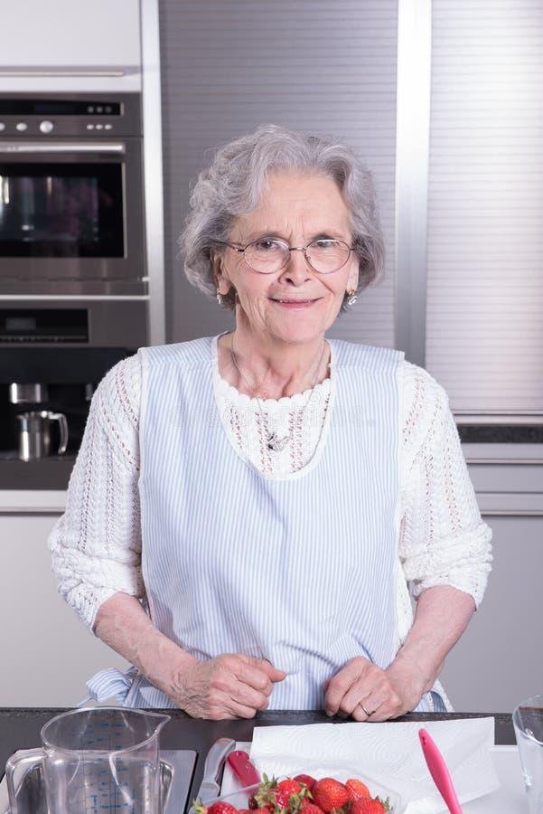 Ο ενεργός θηλυκός συνταξιούχος προετοιμάζει τις φράουλες στην κουζίνα στοκ εικόνες