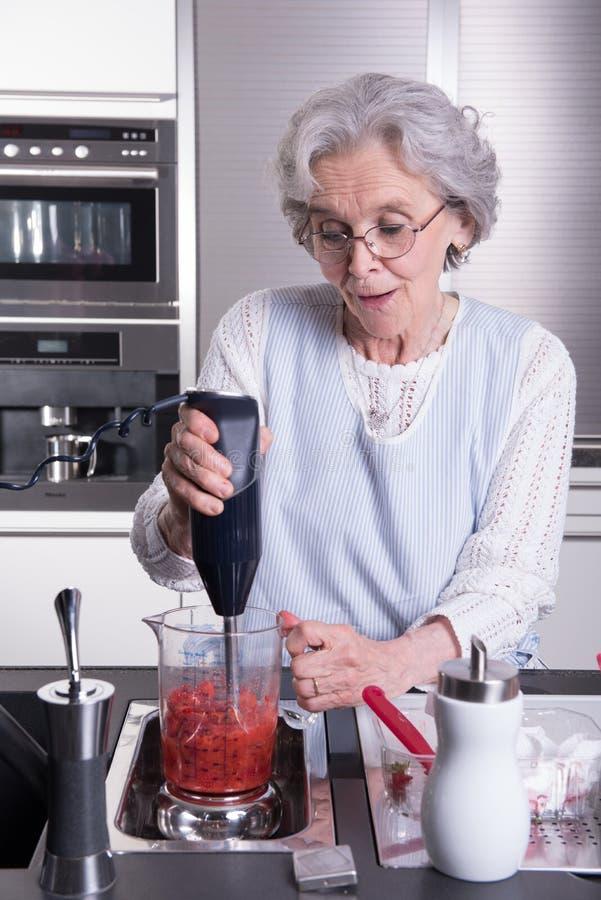 Ο ενεργός θηλυκός συνταξιούχος προετοιμάζει τις φράουλες στην κουζίνα στοκ εικόνες με δικαίωμα ελεύθερης χρήσης