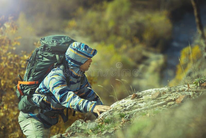 Ο ενεργός οδοιπόρος με το σακίδιο πλάτης αναρριχείται στο βράχο στοκ φωτογραφία με δικαίωμα ελεύθερης χρήσης
