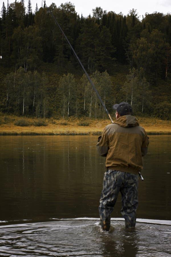 Ο ενιαίος ψαράς σε έναν ήρεμο ποταμό είναι αλιεία φθινοπώρου στοκ εικόνα