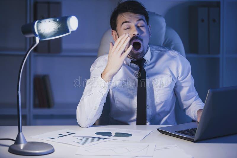 Ο εξαντλημένος νέος επιχειρηματίας χασμουριέται στην εργασία στην αρχή στοκ εικόνες