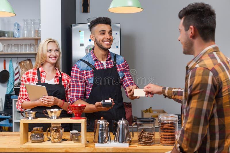 Ο εξυπηρετώντας πελάτης Barista δίνει την κάρτα πληρώνοντας το λογαριασμό στο μετρητή φραγμών καφετεριών στοκ εικόνα