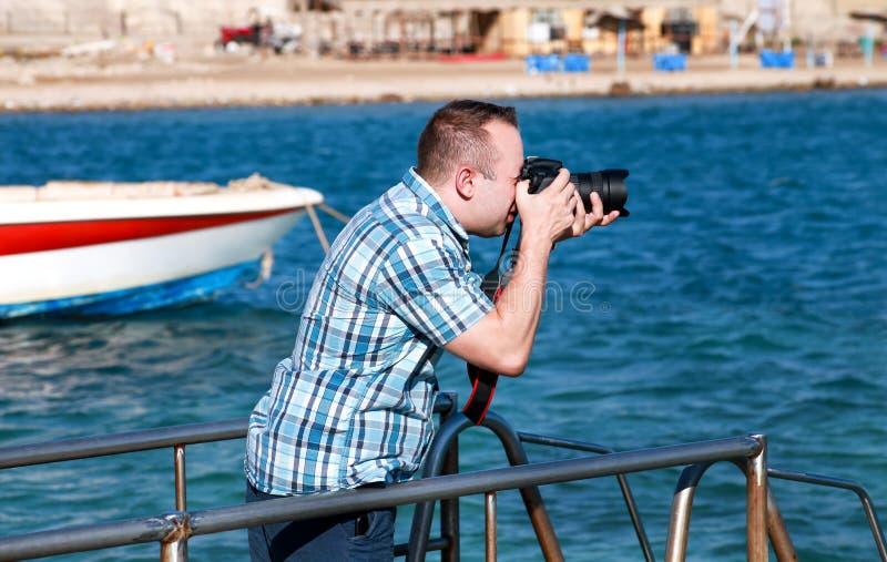 Ο επαγγελματικοί φωτογράφος, ο τουρίστας και ο ταξιδιώτης στην αποβάθρα θάλασσας παίρνουν την εικόνα του περιβάλλοντος, άτομο παρ στοκ εικόνες με δικαίωμα ελεύθερης χρήσης
