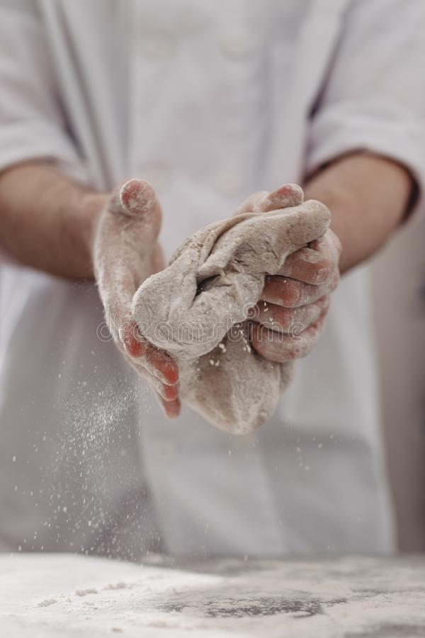 Ο επαγγελματικός αρτοποιός ζυμώνει τη ζύμη σε δικοί του παραδίδει την κουζίνα του αρτοποιείου στοκ φωτογραφίες με δικαίωμα ελεύθερης χρήσης
