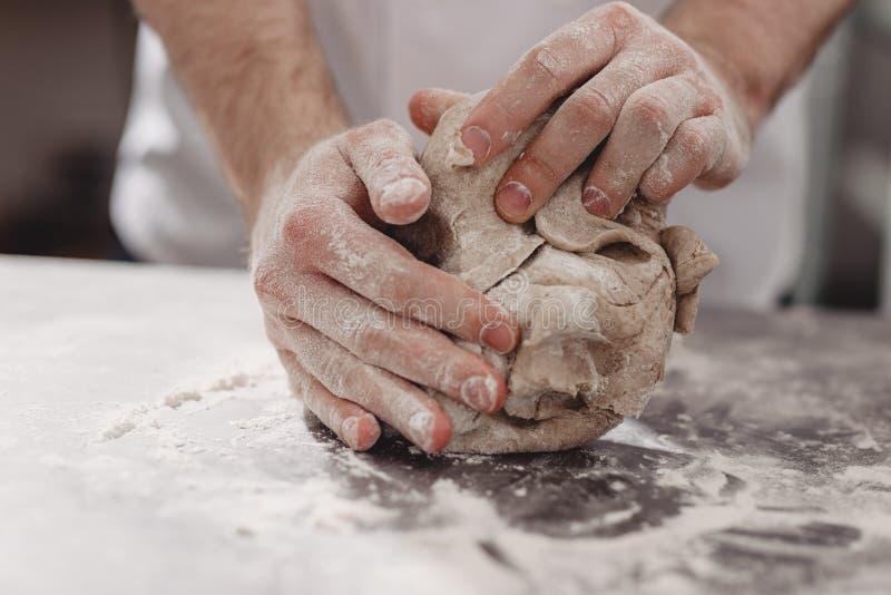 Ο επαγγελματικός αρτοποιός ζυμώνει τη ζύμη στον πίνακα στην κουζίνα του αρτοποιείου στοκ φωτογραφία με δικαίωμα ελεύθερης χρήσης