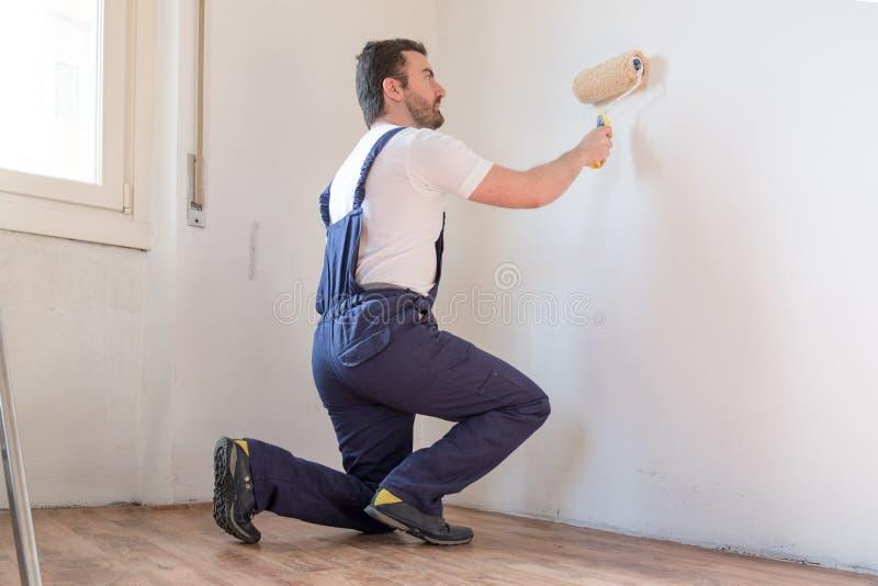 Ο επαγγελματικός εργαζόμενος ζωγράφων χρωματίζει έναν τοίχο στοκ φωτογραφίες
