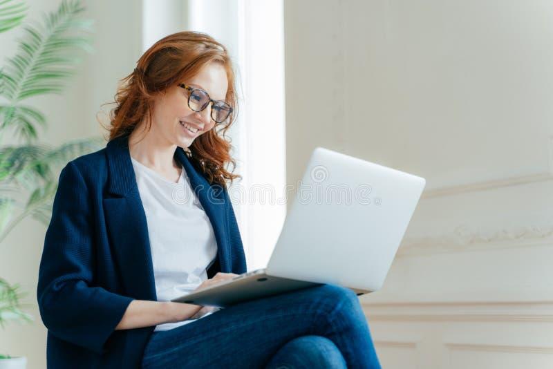 Ο επαγγελματικός θηλυκός εργοδότης απολαμβάνει στη διαδικασία, κάθεται τα διασχισμένα πόδια με τη συσκευή lap-top, κουβεντιάζει o στοκ φωτογραφία με δικαίωμα ελεύθερης χρήσης