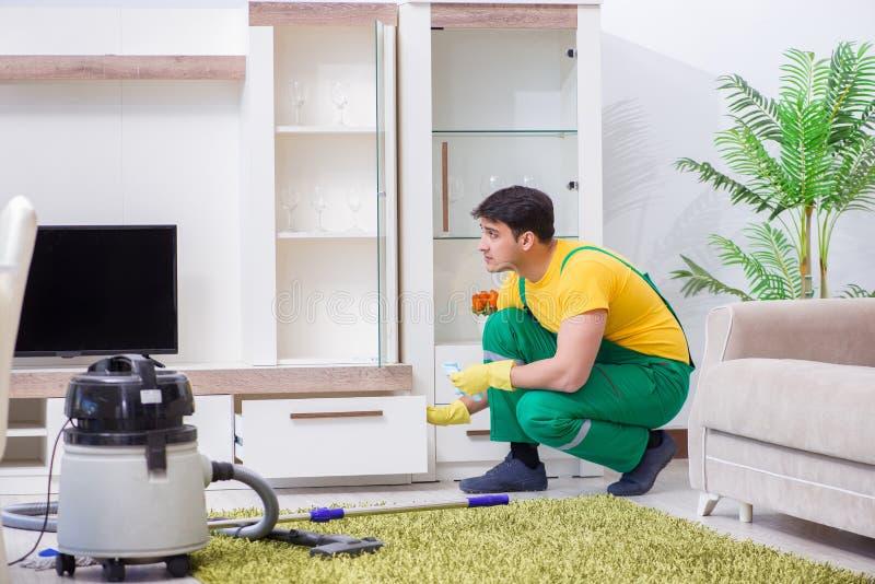 Ο επαγγελματικός καθαρίζοντας ανάδοχος που εργάζεται στο σπίτι στοκ φωτογραφίες