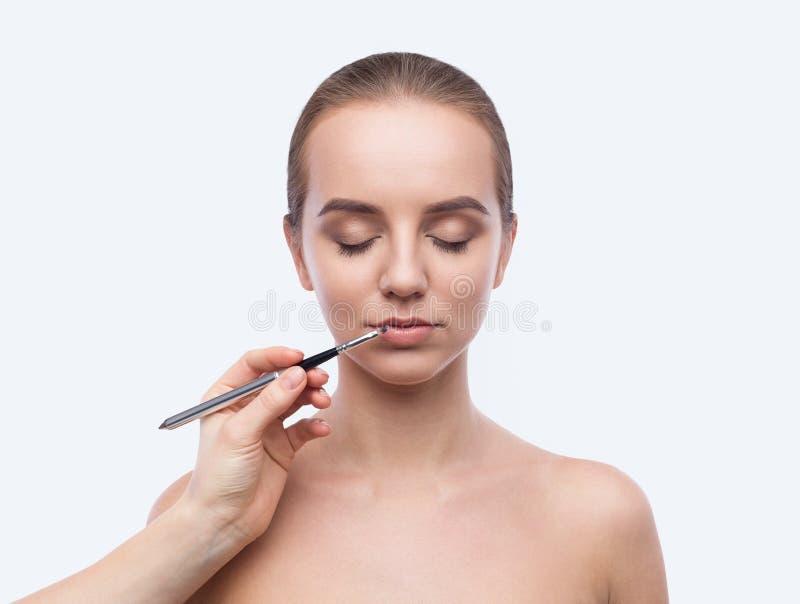 Ο επαγγελματικός καλλιτέχνης visage που εφαρμόζει το χείλι σχολιάζει στο λευκό στοκ εικόνες