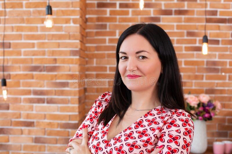 Ο επαγγελματικός ψυχολόγος οικογενειακών γιατρών στα γυαλιά κάθεται στο γραφείο στο ύφος σοφιτών και χαμογελά στη κάμερα στοκ εικόνα